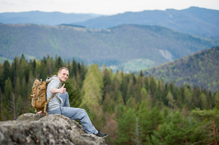 Smiling tourist male with a backpack sitting on the edge of a rock and showing thumb up gesture of good class, with an astonishing blurred view on forest valley and hills Banque d'images