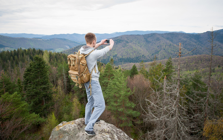 Courageous young man with brown backpack standing on the peak of a rock with back to the camera and makes the photo on the his phone with forest valley and nice hills. Wide angle lens
