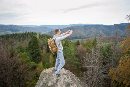 Brave male climber with brown backpack standing on the peak of a rock, with back to the camera and makes the photo on the his phone with forest valley and nice hills.