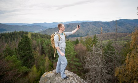 wide angle lens: Young courageous hiker with brown backpack standing on the peak of a rock and makes selfie on the his phone with forest valley and nice hills. Wide angle lens
