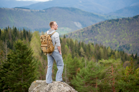 Cool man with a backpack standing on the edge of a rock and looking into the distance on the green forest and nice mountains.