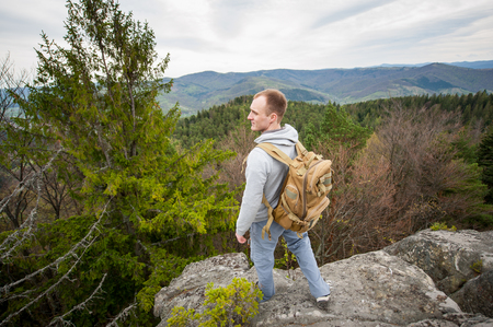 wide angle lens: Profile of man with a backpack standing on the edge of a rock and looking into the distance on the green forest and nice mountains. View from above. Wide angle lens