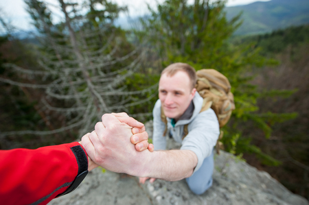 wide angle lens: Close-up of helping hand, hiking help each other. Focus on hands. People teamwork climbing or hiking with motivation and inspiration. Wide angle lens