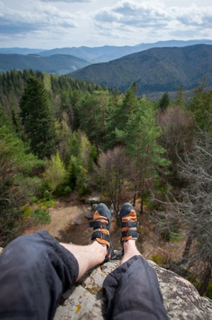 wide angle lens: Focus an astonishing view mountain and forest valley at day with legs and feet in first, freedom concept. Climbing shoes. Wide angle lens Stock Photo