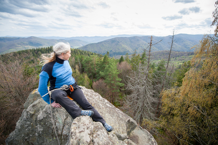Climber woman with climbing equipment sitting on the top of the rock at the background of forest valley and hills. Wide angle lens Stock Photo