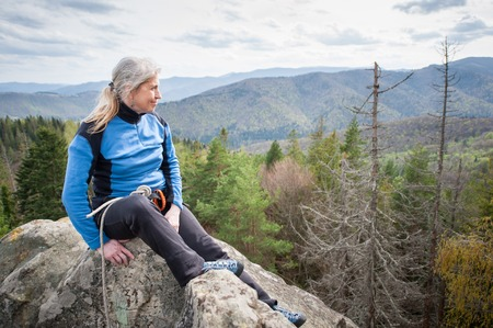 wide angle lens: Old climber female with climbing equipment sitting on the peak of the rock at the background of forest valley and hills. Wide angle lens