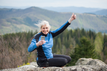 bonne aventure: Smiling woman in a blue jacket sitting on the peak of rock, holding a mobile phone and showing thumb up gesture of good class, on the blurred background of forest valley. Connected Banque d'images