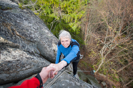 rockclimber: Male rockclimber is helping a climber female to reach a peak of mountain. Man giving a hand to the woman Stock Photo
