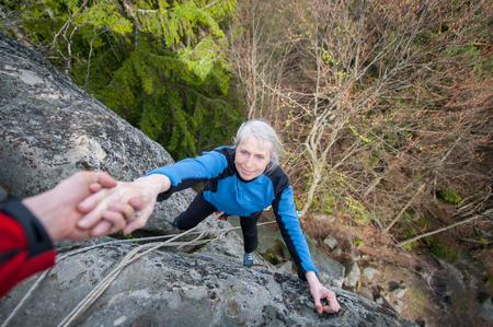 rockclimber: Male rockclimber is helping a climber female to reach a peak of mountain. Man is belaying the woman
