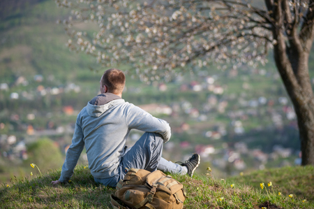 Traveler with a backpack sitting under a blossoming tree on top of hill with green grass and yellow wildflowers and enjoying view to the small village, blurred background. Stock Photo