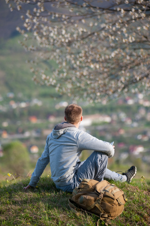 Man with a backpack sitting under a blossoming tree on top of hill with green grass and yellow wildflowers and enjoying view to the small town, blurred background. Vertical picture
