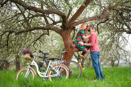 flowered: Romantic couple near the tree and bicycles in spring garden. Female with long blond hair in flowered dress sitting on tree branch and man stand near her. Side view