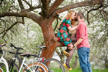 flowered: Romantic couple kissing near the tree and bicycles in spring garden. Woman with long blond hair in flowered dress sitting on tree branch and man stand near her. Side view