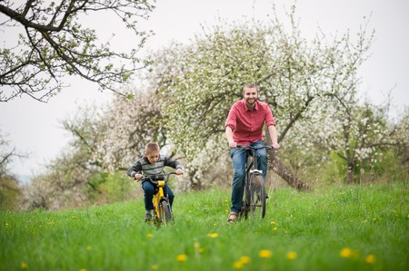 parental love: Happy father and son ride bicycles against the background of blooming trees and fresh greenery. Boys having fun in the spring garden Stock Photo