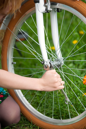 Close-up photo of wrench and girls hand with wedding ring repairing white retro bicycle on the fresh green grass and blooming yellow dandelions.