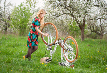 spokes: Girl with long blonde hair in flowered dress standing next to white retro bicycle upside down, exploring the wheel on the green meadow in spring garden Stock Photo