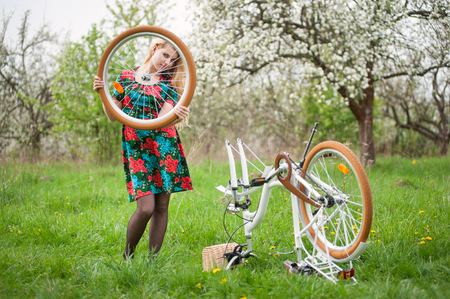 flowered: Young woman with long blonde hair in flowered dress standing next to white retro bicycle upside down and holding in hand a wheel that is removed from bike on the green grass.