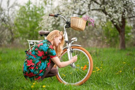 flowered: Young blonde female in flowered dress repairing her white vintage bicycle in the spring garden