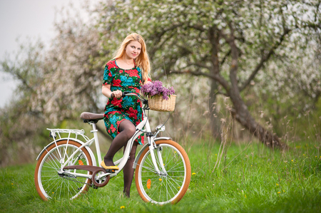 flowered: Young woman with long blond hair wearing flowered dress and yellow shoes starting to ride a vintage white bicycle with flowers basket