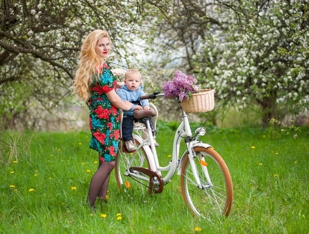 flowered: Young blonde mother with long hair and red lips in flowered dress holding son in bicycle chair, in the basket lay a bouquet of lilacs, against of blooming trees, dandelions in spring garden Stock Photo