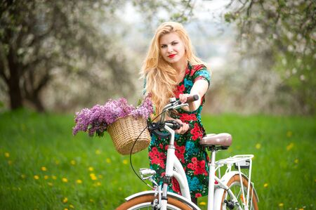 flowered: Girl with long blond hair wearing flowered dress looking at the camera keeps vintage white bicycle with flowers basket, against the blurred background of trees, greenery in spring garden. Front view