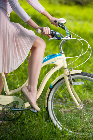 Photo of hands of a girl holding handbrake on vintage bicycle and graceful leg at the pedal on the blurred background of fresh greenery. Close-up
