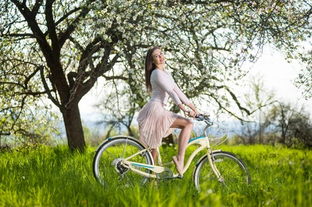 day flowering: Smiling girl wearing white dress riding bicycle and sexually posing against the background of flowering trees in spring garden at the sunny day Stock Photo