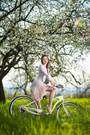 belles jambes: Beautiful woman wearing white dress sitting astride on bicycle and sexually posing