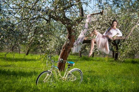 Elegant young female in light dress sitting on a branch of a blossoming tree near develops shawl and retro bicycle standing at the green grass in the spring garden.