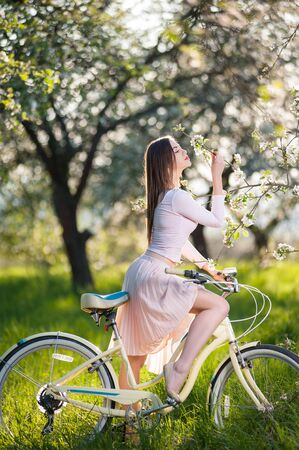 Pretty girl, with a bicycle in the lush green grass, smelling a flowers from a branch of a blossoming tree in the ray of sunshine in a spring garden