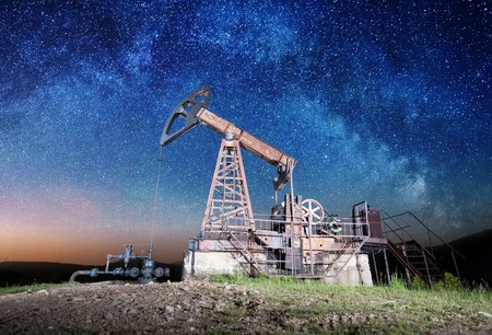 Petroleum industry equipment pumping crude oil in the night under Starry Sky