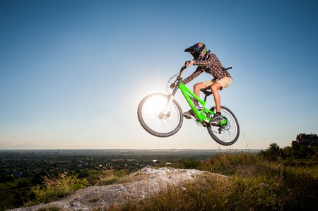 mtb: Bicyclist riding downhill and making extreme jump on a mountain bike into the distance from the slope in the mountains against blue sky with sun. Wide angle view