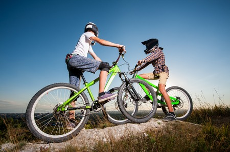 Two cyclists getting ready to riding downhill on the mountain bikes from the top of the hill under blue sky. Men looking into the distance. Bottom wide angle view