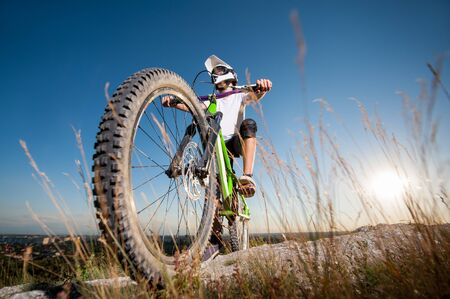 Cyclist in helmet and glasses stay on the bicycle at the hill under blue sky and sun and looking into the distance. Focus on the bike. Bottom point view