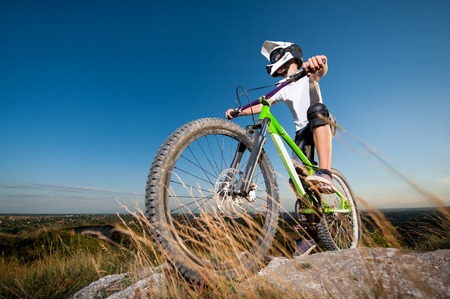Athlete bicyclist in helmet and glasses getting ready to ride downhill on the mountain bike from the top of mountain under blue sky. Wide angle view