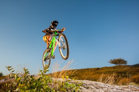 Cyclist in helmet and glasses jumping on a mountain bike on the hill against blue sky. Dangerous downhill. Bottom view