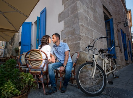 tenderly: Lovely couple sitting in sidewalk cafe near their tandem bicycle. They tenderly looking at each other. Lviv, Ukraine Stock Photo