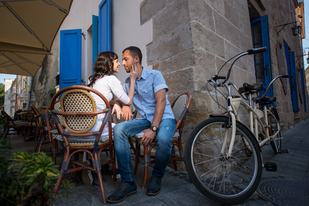 tenderly: Loving couple sitting in sidewalk cafe near their tandem bike. Wifes hand gently concerns cheeks her husband, they tenderly looking at each other