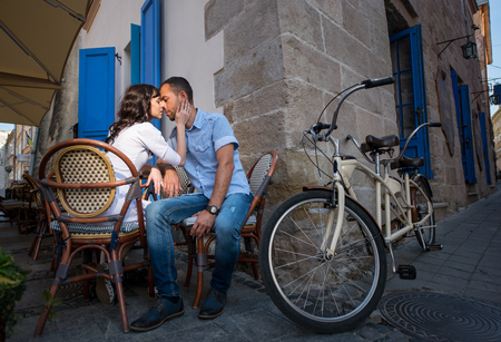 tenderly: Loving couple sitting in sidewalk cafe near their tandem bicycle. They tenderly looking at each other. Lviv, Ukraine Stock Photo