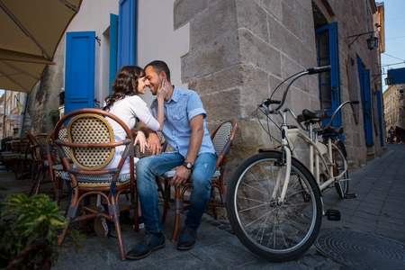 tenderly: Loving couple sitting in sidewalk cafe near their tandem bike. Womans hand gently concerns cheeks her boyfriend, they tenderly looking at each other and smiling Stock Photo