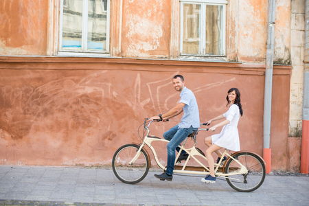 Young couple riding on tandem bicycle at the street city against the background of the old orange wall with windows. They looking to the camera and smiling