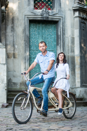 Happy couple riding on vintage tandem bicycle against the backdrop of historic building. They smiling and looking to the camera. Lviv, Ukraine