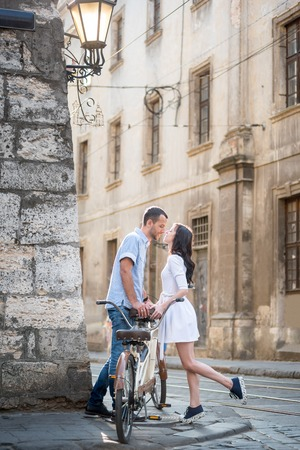would: Man and woman are drawn to each other that would kiss near retro tandem bike in urban environment on the narrow old streets. Lviv, Ukraine Stock Photo