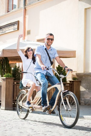 Young couple in sunglasses riding on tandem bicycle on the city at the sunny day. The man runs a bicycle, a girl waving hand Standard-Bild