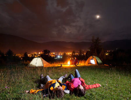 Twosome admiring the bright stars and lying on the grass in the background night tent camping with their friends near campfire, mighty mountains, luminous town Stock Photo