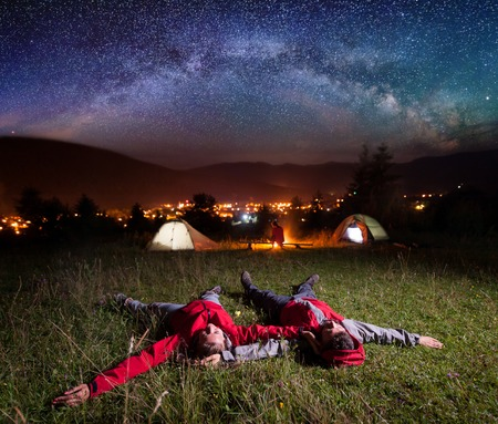 Loving couple admiring the bright stars and lying on the grass in the background night tent camping with their friend near campfire, mighty mountains, luminous town