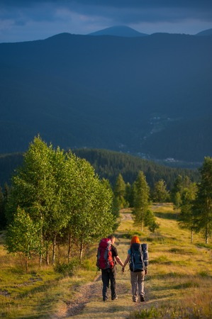 Rear view couple tourists with backpacks walking along a beautiful mountain area holding hands. Lifestyle active vacations concept mountains landscape on background Stock Photo