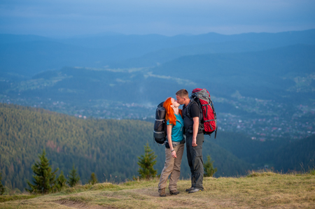 Hikers guy and red-haired woman kissing on the road in the mountain on the background of the landscaped mighty mountains Reklamní fotografie