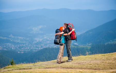 Happy hikers is embracing, standing with backpacks on the road in the mountain with beautiful mountain landscape on blurred background. Copy space