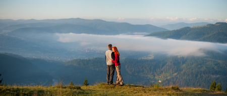 Romantic couple hikers hugging and enjoying beautiful mountain landscape with morning haze over the mountains and forests. Panorama